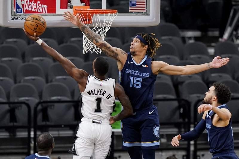 San Antonio Spurs guard Lonnie Walker IV (1) is defended by Memphis Grizzlies forward Brandon Clarke (15) as he tries to score during the first half of an NBA basketball game in San Antonio, Monday, Feb. 1, 2021.