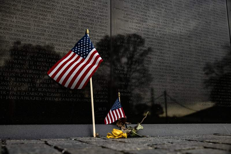 A flower and two American flags are left at the base of the Vietnam Veterans Memorial Wall on Veterans Day on November 11, 2020 in Washington, DC. Veterans Day is when Americans honor those who served the country in the Armed Forces. The Vietnam Veterans Memorial Wall contains 58,320 names of those who gave their lives during the conflict in Vietnam. It was designed by Maya Lin and was completed in 1982. (Photo by Samuel Corum/Getty Images)