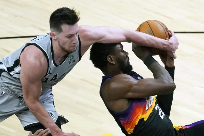 San Antonio Spurs forward Drew Eubanks (14) blocks the shot of Phoenix Suns center Deandre Ayton during the second half of an NBA basketball game Saturday, April 17, 2021, in Phoenix.