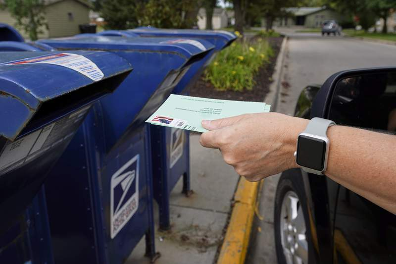 """A person drops into a mail box applications for mail-in ballots, in Omaha, Neb., Tuesday, Aug. 18, 2020. The Postmaster general announced Tuesday he is halting some operational changes to mail delivery that critics warned were causing widespread delays and could disrupt voting in the November election. Postmaster General Louis DeJoy said he would """"suspend"""" his initiatives until after the election """"to avoid even the appearance of impact on election mail."""" (AP Photo/Nati Harnik)"""