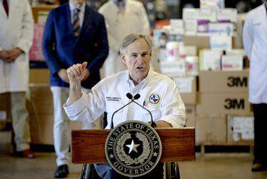 Gov. Greg Abbott gestures to boxes of personal protective equipment during a press conference about the state's response to the coronavirus on Tuesday, March 24, 2020, in Austin. (Nick Wagner/POOL via American-Statesman)