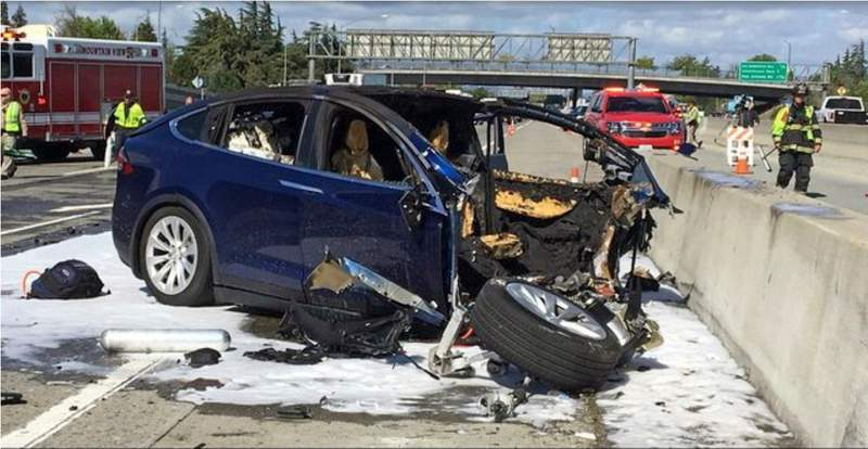 FILE - In this March 23, 2018, file photo provided by KTVU, emergency personnel work a the scene where a Tesla electric SUV crashed into a barrier on U.S. Highway 101 in Mountain View, Calif. The Apple engineer who died when his Tesla Model X crashed into the concrete barrier complained before his death that the SUVs Autopilot system would malfunction in the area where the crash happened. The complaints were detailed in a trove of documents released Tuesday, Feb. 11, 2020, by the U.S. National Transportation Safety Board, which is investigating the March, 2018 crash that killed engineer Walter Huang.  (KTVU-TV via AP, File)
