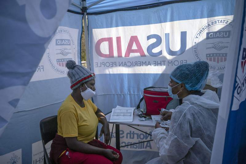 FILE - In this July 2, 2020 file photo, nurse Nomautanda Siduna, right, talks to a patient who is HIV-positive inside a gazebo used as a mobile clinic in Ngodwana, South Africa. Researchers are stopping a study early after finding that a shot of an experimental medicine every two months worked better than daily Truvada pills to help keep uninfected women from catching HIV from an infected sex partner.  The news is a boon for AIDS prevention efforts especially in Africa, where the study took place, and where women have few discreet ways of protecting themselves from infection.  (AP Photo/Bram Janssen, File)