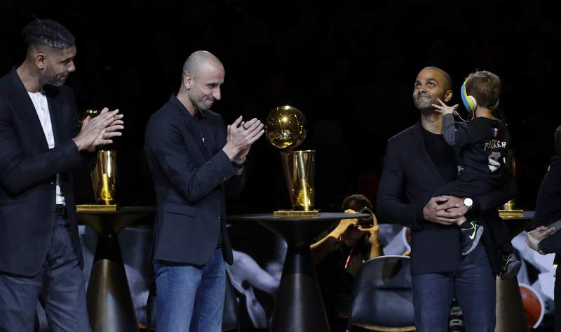 Former San Antonio Spurs guard Tony Parker, right, with former teammates Tim Duncan, left, and Manu Ginobili, center, watches as his jersey is unveiled during his retirement ceremony after the team's NBA basketball game against the Memphis Grizzlies in San Antonio, Monday, Nov. 11, 2019. (AP Photo/Eric Gay)