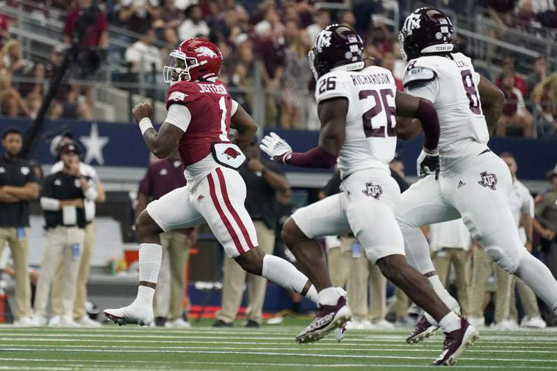 Arkansas quarterback KJ Jefferson (1) runs the ball as Texas A&M defensive back Demani Richardson (26) and defensive lineman DeMarvin Leal (8) give chase in the first half of an NCAA college football game in Arlington, Texas, Saturday, Sept. 25, 2021.