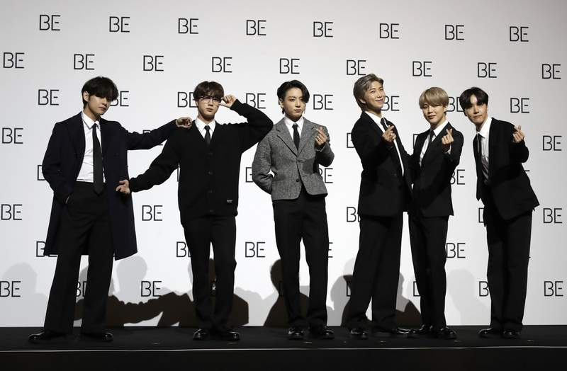 """File---File photo taken Nov.20, 2020 members of South Korean K-pop band BTS pose for photographers during a press conference to introduce their new album """"BE"""" in Seoul, South Korea. (AP Photo/Lee Jin-Man, file)"""
