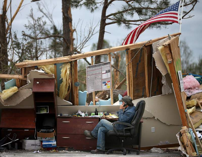A man who wished not to be identified talks on a phone in a business that was destroyed by a tornado April 30, 2014 in Mayflower, Arkansas. Deadly tornadoes ripped through the region, leaving more than two dozen dead.