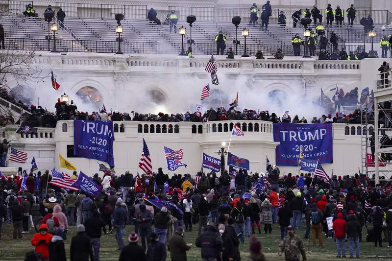 FILE - In this Wednesday, Jan. 6, 2021, file photo, violent protesters, loyal to President Donald Trump, storm the Capitol, in Washington. Federal prosecutors say a retired Air Force officer who was part of the mob that stormed the U.S. Capitol was arrested Sunday, Jan. 10, 2021, in Texas. (AP Photo/John Minchillo, File)