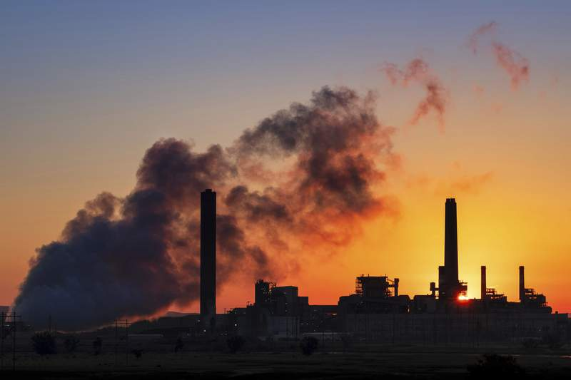 FILE - In this July 27, 2018, file photo, the Dave Johnston coal-fired power plant is silhouetted against the morning sun in Glenrock, Wyo. Wyoming's governor is promoting a Trump administration study that says capturing carbon dioxide emitted by coal-fired power plants would be an economical way to curtail the pollution  findings questioned by a utility that owns the plants and wants to shift away from the fossil fuel in favor of wind and solar energy. Supporters say carbon capture would save coal by pumping carbon dioxide  a greenhouse gas emitted by power plants  underground instead of into the atmosphere. (AP Photo/J. David Ake, File)