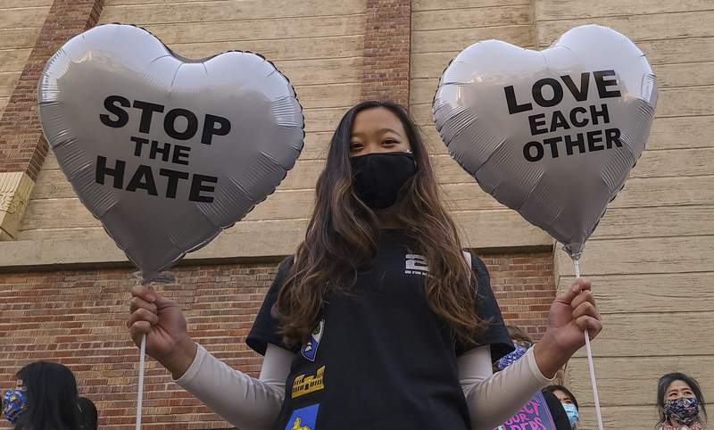 """FILE - In this March 13, 2021, file photo, Chinese-Japanese American student Kara Chu, 18, holds a pair of heart balloons decorated by herself for the rally """"Love Our Communities: Build Collective Power"""" to raise awareness of anti-Asian violence outside the Japanese American National Museum in Little Tokyo in Los Angeles. The shootings at three Georgia massage parlors and spas Tuesday, March 16, that left eight people dead, six of them women of Asian descent, come on the heels of a recent wave of attacks against Asian Americans since the coronavirus first entered the United States. (AP Photo/Damian Dovarganes, File)"""