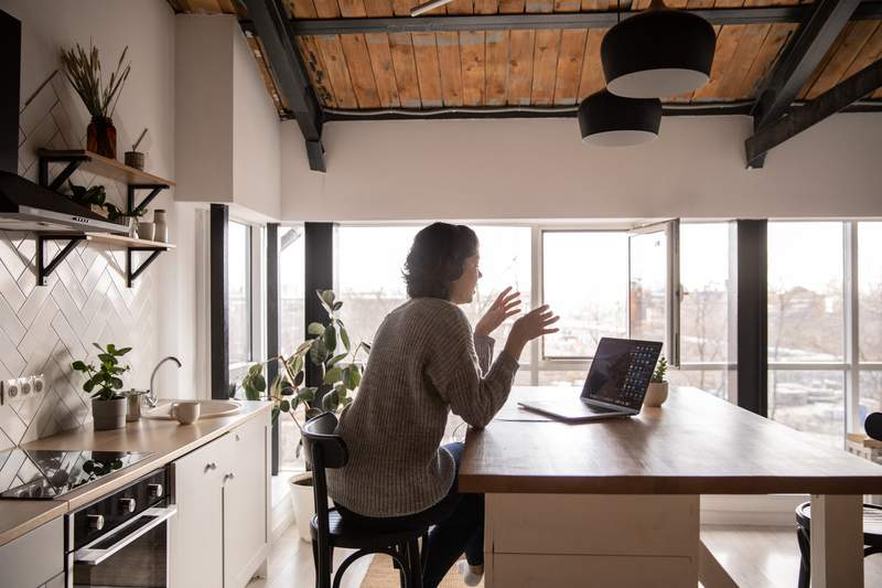 A woman sits at her computer.