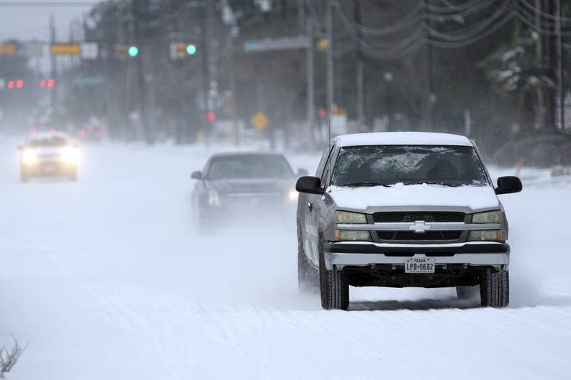 Vehicles drive on snow and sleet covered roads Monday, Feb. 15, 2021, in Spring, Texas. (AP Photo/David J. Phillip)