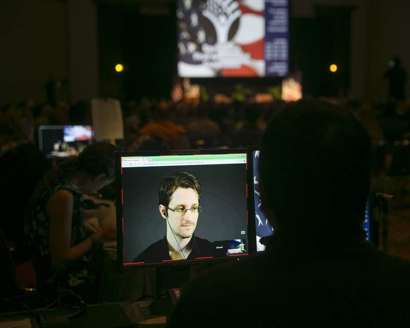 FILE  - In this Saturday, Feb. 14, 2015 file photo, a video technician monitors a computer screen as National Security Agency leaker Edward Snowden appears on a live video feed broadcast from Moscow at an event sponsored by the ACLU Hawaii in Honolulu. Former U.S. security contractor Edward Snowden says he will apply for Russian citizenship but not renounce his U.S. citizenship. The former contractor for the National Security Agency has been living in Russia since 2013 to escape prosecution in the U.S. after leaking classified documents detailing government surveillance programs. (AP Photo/Marco Garcia, File)