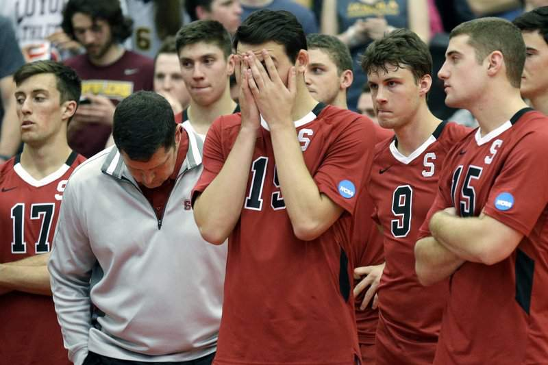 FILE - In this May 3, 2014, file photo, Stanford men's volleyball head coach John Kosty, second from left, looks down as players react after a 3-1 loss to Loyola in the NCAA men's college volleyball championship at Gentile Arena in Chicago. Stanford announced Wednesday, July 8, 2020, that it is dropping 11 sports amid financial difficulties caused by the coronavirus pandemic. The school will discontinue men's and women's fencing, field hockey, lightweight rowing, men's rowing, co-ed and women's sailing, squash, synchronized swimming, men's volleyball and wrestling after the 2020-21 academic year. Stanford also is eliminating 20 support staff positions.