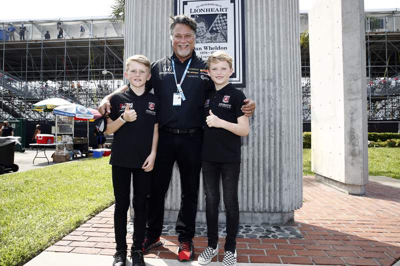 This photo provided by IndyCar, Saturday, April 24, 2021, shows Michael Andretti, center, with Sebastian and Oliver Wheldon below the monument of their late father on Dan Wheldon Way in St. Petersburg, Fla. Andretti Autosport on Saturday announced it had signed the sons of the two-time Indianapolis 500 winner to junior driver development deals. Wheldon was killed in 2011 in the IndyCar season finale, five months after winning his second Indy 500. His sons were 2 and 8 months at the time he was killed. (Chris Owens/IndyCar via AP)