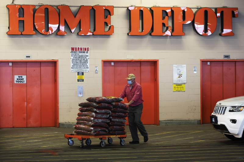 FILE - In this April 3, 2020 file photo, a Home Depot customer pushes a cart loaded with supplies in New York. Home Depot is buying HD Supply Co.,  a distributor of maintenance, repair and operations products in the multifamily and hospitality end markets, in a deal valued at about $8 billion. The transaction is expected to close during Home Depot's fiscal fourth quarter. (AP Photo/Mark Lennihan, File)