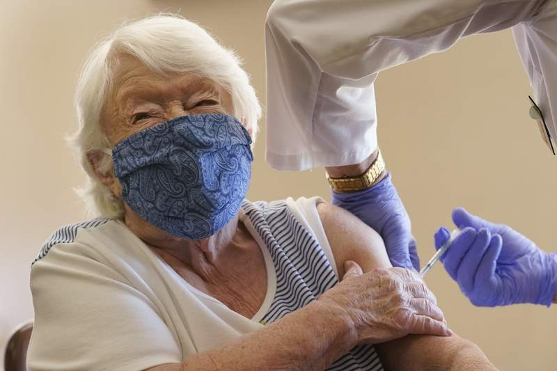 Nathalie Avery, 90, reacts as she gets the COVID-19 vaccine, Thursday, Jan. 21, 2021, at the Isles of Vero Beach assisted and independent senior living community in Vero Beach, Fla. (AP Photo/Wilfredo Lee)