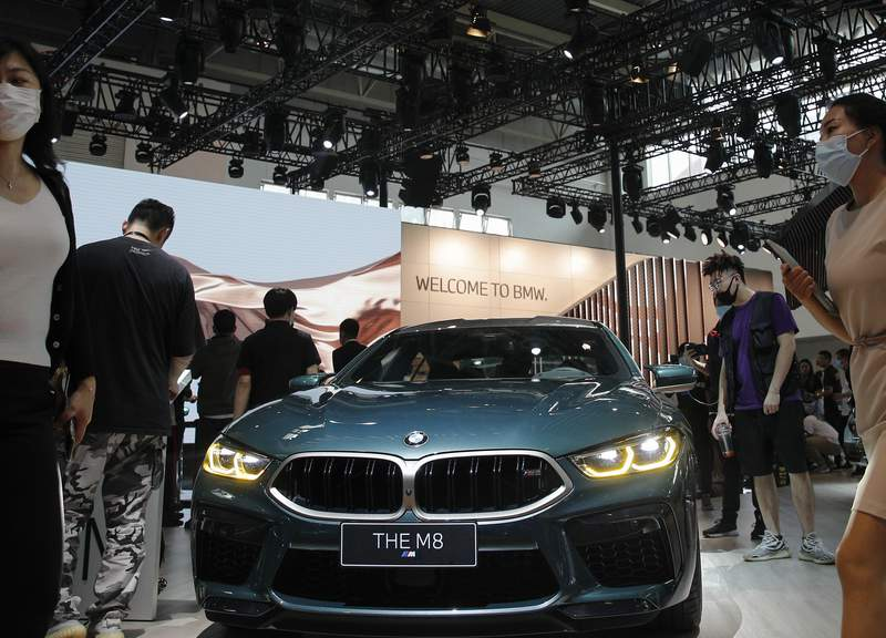FILE - In this Sept. 27, 2020 file photo, visitors gather near a BMW M8 model on display at the Auto China 2020 show in Beijing, China.  In figures released Thursday March 11, 2021, BMW saw profits fall by 23% last year as the pandemic shuttered factories in the early part of the year, but the company said Thursday that earnings bounced back strongly in the second half of 2020. (AP Photo/Andy Wong, File)
