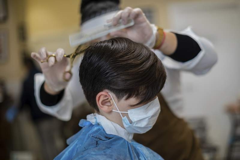 A child gets a haircut at a barber shop in Madrid, Spain, Monday, May 4, 2020. Spaniards will be able to get a haircut, buy glasses or take away food as long as they have previously made an appointment and they travel on public transport with mouth and nose covered with mandatory masks. The country enters the first stage of its 4-phase lockdown rollback helped by the lowest daily reports of coronavirus related deaths from coronavirus in 1.5 months. (AP Photo/Bernat Armangue)