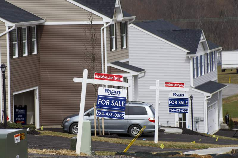 Model homes and for sale signs line the streets as construction continues at a housing plan in Zelienople, Pa., Wednesday, March 18, 2020. U.S. home sales jumped in February to their highest level in 13 years, a trend that will almost certainly be reversed as the viral outbreak keeps more people at home.  (AP Photo/Keith Srakocic)
