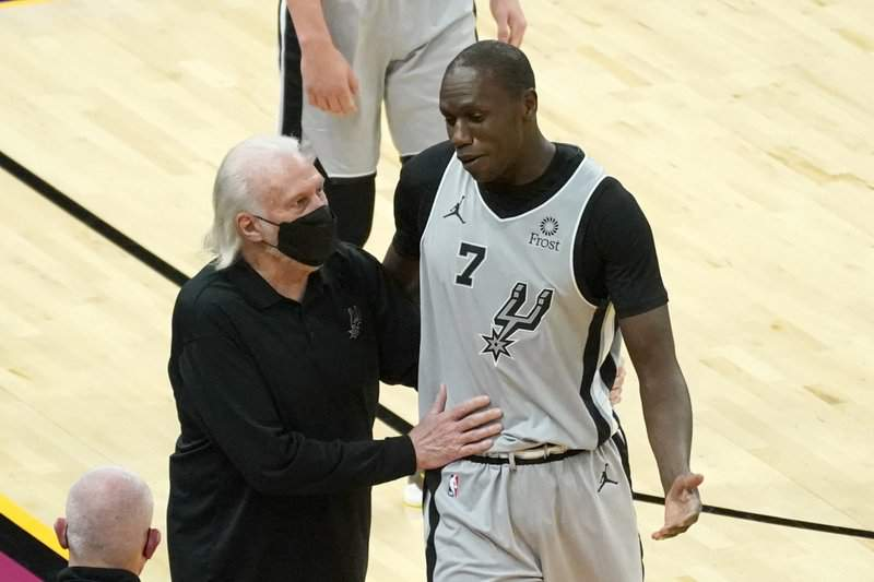 San Antonio Spurs center Gorgui Dieng (7) talks to coach Gregg Popovich after being ejected during the second half of the team's NBA basketball game against the Phoenix Suns, Saturday, April 17, 2021, in Phoenix.
