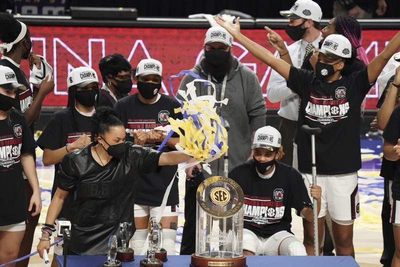 South Carolina head coach Dawn Staley puts streamers on a trophy after an NCAA college basketball game against Georgia Sunday, March 7, 2021, during the Southeastern Conference tournament final in Greenville, S.C. (AP Photo/Sean Rayford)