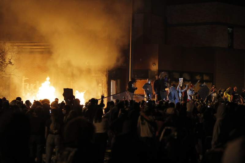 Protesters gather in front of the burning Minneapolis police 3rd Precinct building Thursday, May 28, 2020, in Minneapolis. (AP Photo/Julio Cortez)