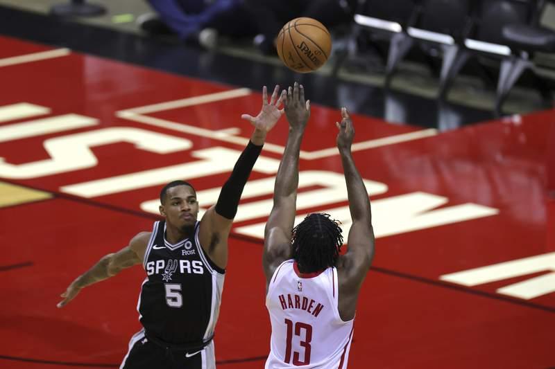 FILE - Houston Rockets' James Harden (13) puts up a basket ahead of San Antonio Spurs defender Dejounte Murray (5) during the third quarter of an NBA basketball game in Houston, Thursday, Dec. 17, 2020. (Carmen Mandato/Pool Photo via AP)