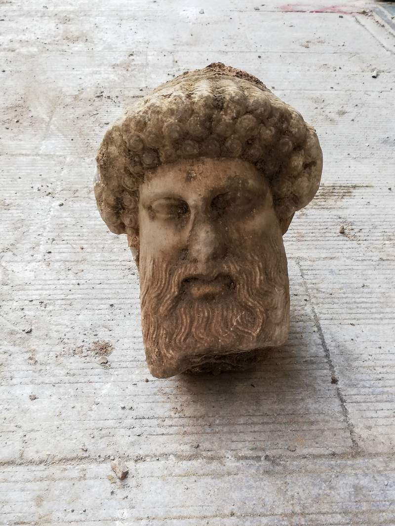 """In this undated photo, provided by the Greek Culture Ministry on Sunday, Nov. 15, 2020, a head of the ancient god Hermes is pictured after being found during sewage works in central Athens. The ministry said Sunday that the head, depicting Hermes at a """"mature age"""", one of many that served as street markers in ancient Athens, appears to be from around 300 BC, that is, either from the late 4th century BC, or the early 3rd century. (Greek Culture Ministry via AP)"""