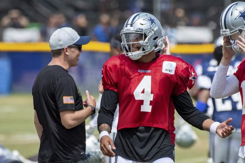 Dallas Cowboys quarterback Dak Prescott (4) talks with offensive coordinator Kellen Moore, left, during practice at the NFL football team's training camp in Oxnard, Calif., Wednesday, July 28, 2021. (AP Photo/Michael Owen Baker)