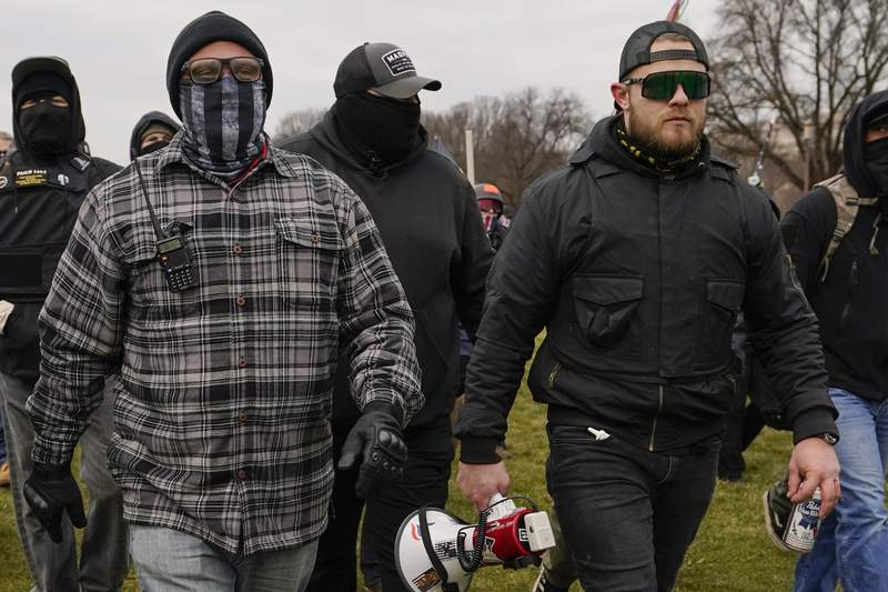 FILE - In this Jan. 6, 2021, file photo, Proud Boys members Joseph Biggs, left, and Ethan Nordean, right with megaphone, walk toward the U.S. Capitol in Washington. A federal judge has ordered Biggs and Nordean, two leaders of the far-right Proud Boys extremist group, to be arrested and jailed while awaiting trial on charges they planned and coordinated an attack on the U.S. Capitol to stop Congress from certifying President Joe Bidens electoral victory. The two had been free since their March 10 indictment, but U.S. District Judge Timothy Kelly concluded April 19, that the two men are dangerous and won't abide by release conditions. (AP Photo/Carolyn Kaster, File)