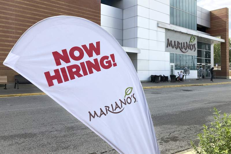 A sign in the parking lot of Mariano's grocery store advertises the availability of jobs Friday, Oct. 8, 2021, in Chicago.  One reason Americas employers are having trouble filling jobs was starkly illustrated in a report Tuesday, Oct. 12: Americans are quitting in droves.  (AP Photo/Charles Rex Arbogast)