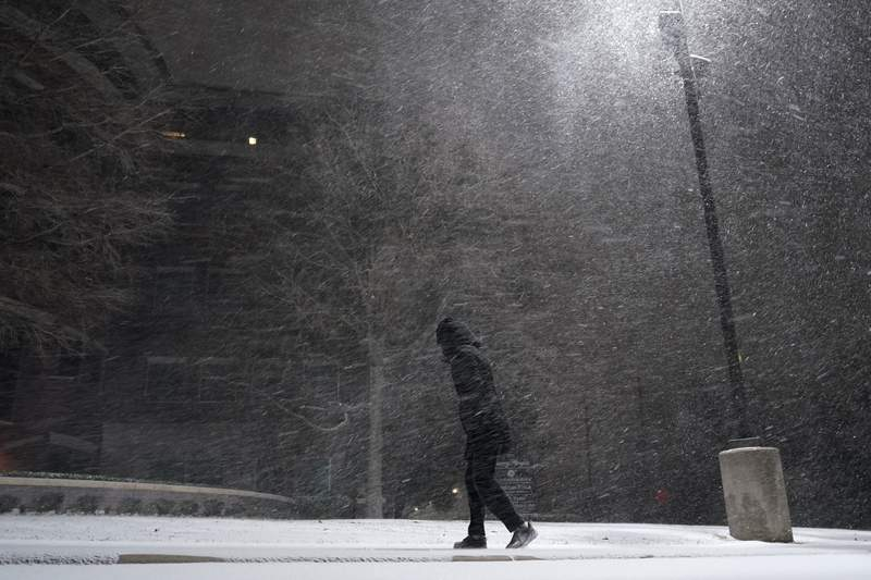 FILE - In this Feb. 14, 2021, file photo, woman walks through falling snow in San Antonio. As temperatures plunged and snow and ice whipped the state, much of Texas' power grid collapsed, followed by its water systems. Tens of millions huddled in frigid homes that slowly grew colder or fled for safety. (AP Photo/Eric Gay, File)