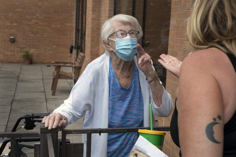 Kay Foley, 88, left and her daughter Chris Coverdale blow kisses to each other after an outdoor visit, Tuesday, July 21, 2020, at Jones-Harrison nursing home, amid the coronavirus pandemic, in Minneapolis. (Jerry Holt/Star Tribune via AP)