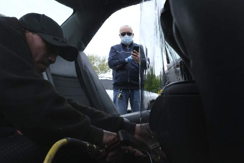 FILE - In this  May 6, 2020, file photo, Luis Hidalgo, wearing face mask, watches as Joel Rios installs a plastic barrier in his car to protect himself and his passengers from the new coronavirus in the Bronx borough of New York. Mask slackers will now have to provide photographic proof they're wearing a face covering before boarding an Uber. The San Francisco-based company unveiled a new policy Tuesday, Sept. 1, stipulating that if a driver reports to Uber that a rider wasnt wearing a mask, the rider will have to take a selfie with one strapped on the next time they summon a driver on the worlds largest ride-hailing service. (AP Photo/Seth Wenig, File)