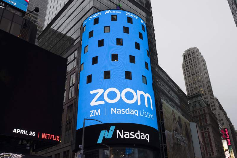 FILE - This April 18, 2019, file photo shows a sign for Zoom Video Communications ahead of the company's Nasdaq IPO in New York. Zooms videoconferencing service is deepening its integral role in life during the coronavirus pandemic as tens of thousands more businesses and other users pay for subscriptions to get more control over their virtual meetings. The surge in paying customers enabled Zoom to hail another quarter of astounding growth in a report released Monday, Aug. 31, 2020. (AP Photo/Mark Lennihan, File)