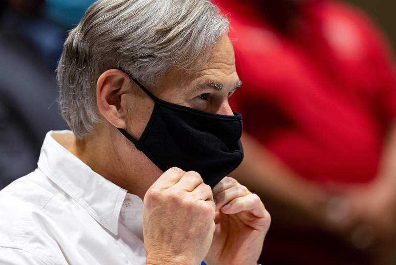Gov. Greg Abbott puts on his mask during his press conference after talking to local and county officials about the damage done by Hurricane Hanna in Nueces and Kleberg counties on July 28, 2020. (Credit: Courtney Sacco/Caller-Times via REUTERS)