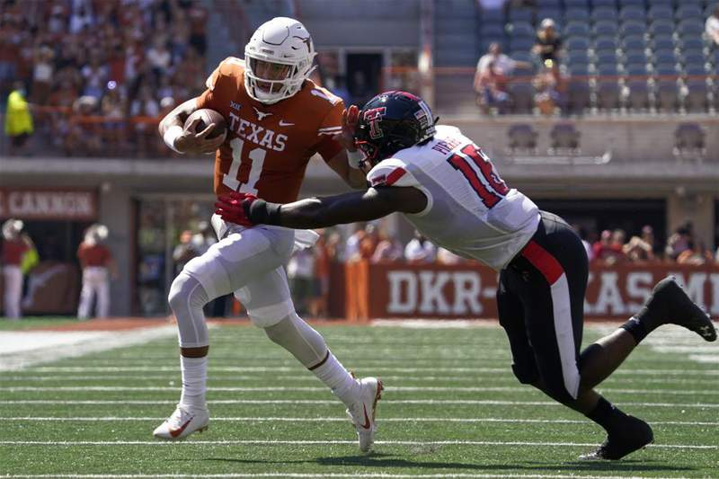 Texas quarterback Casey Thompson (11) tries to run past Texas Tech linebacker Jesiah Pierre (16) during the first half of an NCAA college football game on Saturday, Sept. 25, 2021, in Austin, Texas.