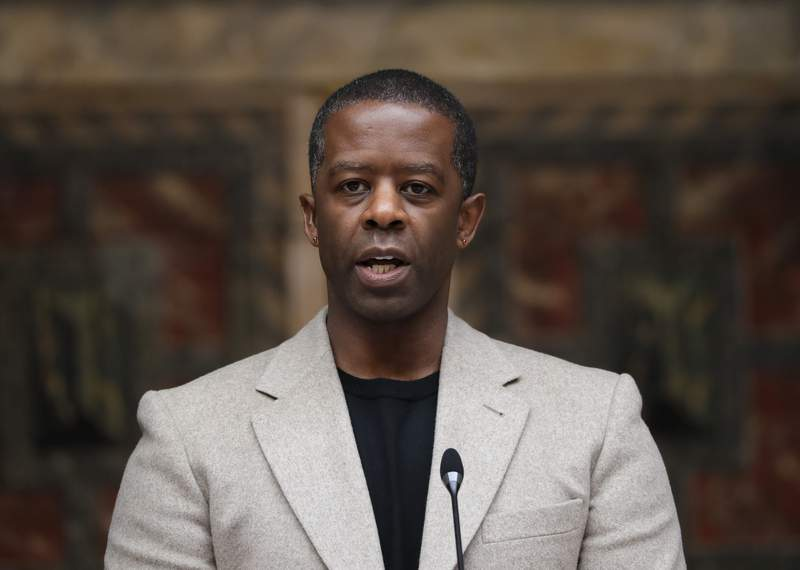 FILE - In this May 10, 2021 file photo, British actor Adrian Lester speaks on stage at the official signing in ceremony for Sadiq Khan as the Mayor of London at Shakespeare's Globe Theatre in London.  The Lehman Trilogy was able to make only four preview performances on Broadway before the pandemic shut its doors. Now it plans to return to tell the story of an American financial giants downfall with a new cast member. Stefano Massinis play about what led to the collapse of Lehman Brothers  adapted by Ben Power and directed by Sam Mendes  will add Adrian Lester, replacing Ben Miles, and joining Simon Russell Beale and Adam Godley.   (AP Photo/Kirsty Wigglesworth, File)