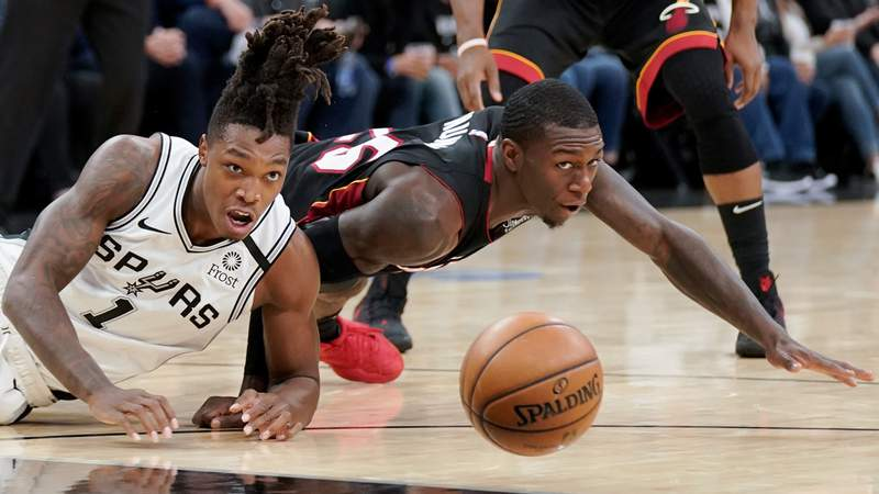 San Antonio Spurs' Lonnie Walker IV and Miami Heat's Kendrick Nunn fall as they chase the ball during the first half of an NBA basketball game, Sunday, Jan. 19, 2020, in San Antonio.
