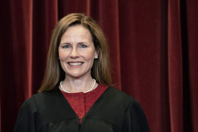 FILE - In this April 23, 2021, file photo Supreme Court Justice Amy Coney Barrett stands during a group photo at the Supreme Court in Washington. Barrett has refused to block a plan by Indiana University to require students and employees to get vaccinated against COVID-19. Barrett's action came in response to an emergency request from eight students, and it marked the first time the high court has weighed in on a vaccine mandate. (Erin Schaff/The New York Times via AP, Pool)