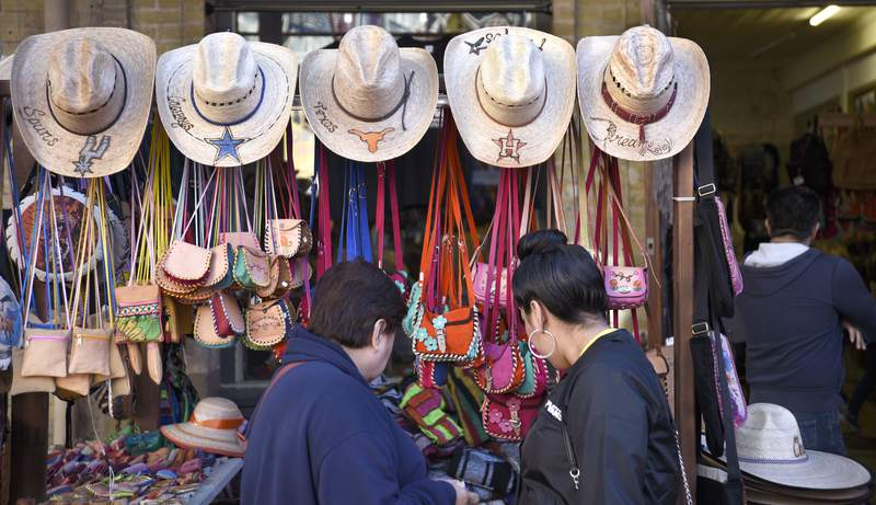 Two women look at handmade merchandise in a display of hats and other souvenir items at a shop in the Historic Market Square, also known as El Mercado, in San Antonio, Texas. (Photo by Robert Alexander/Getty Images)
