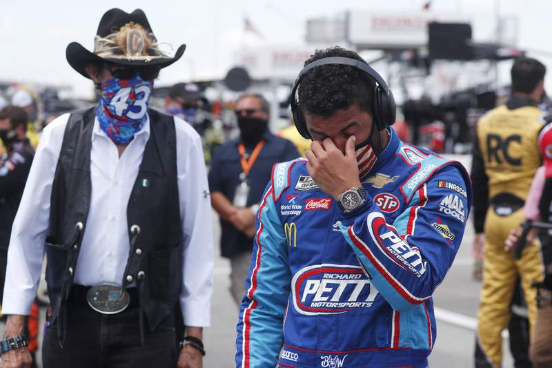 Driver Bubba Wallace, right, is overcome with emotion as he and team owner Richard Petty walk to his car in the pits of the Talladega Superspeedway prior to the start of the NASCAR Cup Series auto race at the Talladega Superspeedway in Talladega Ala., Monday June 22, 2020. In an extraordinary act of solidarity with NASCARs only Black driver, dozens of drivers pushed the car belonging to Bubba Wallace to the front of the field before Mondays race as FBI agents nearby tried to find out who left a noose in his garage stall over the weekend. (AP Photo/John Bazemore)