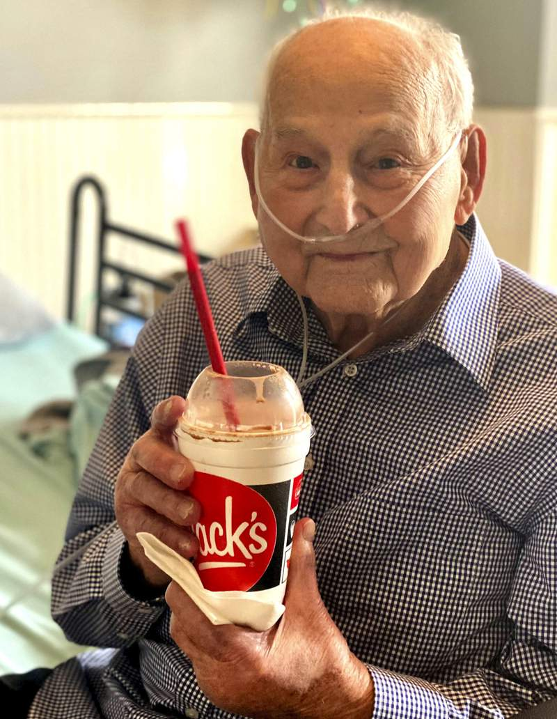 In this photo provided by Holly Wooten McDonald, World War II veteran and COVID-19 survivor Major Wooten holds a celebratory milkshake on his 104th birthday on Thursday, Dec. 3, 2020, in Madison, Alabama. Wooten was released from the hospital this week after contracting the illness caused by the new coronavirus before Thanksgiving. (Holly Wooten McDonald via AP)