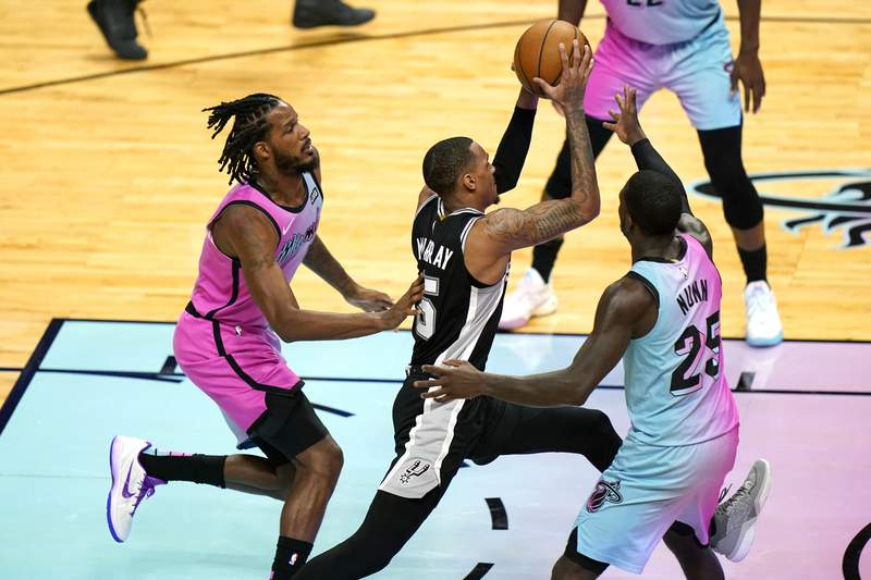 San Antonio Spurs guard Dejounte Murray (5) drives to the basket as Miami Heat forward Trevor Ariza, left, and guard Kendrick Nunn (25) defend during the second half of an NBA basketball game Wednesday, April 28, 2021, in Miami. (AP Photo/Lynne Sladky)