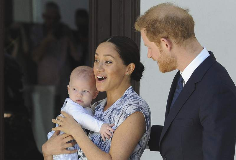 FILE - In this Wednesday, Sept. 25, 2019 file photo, Britain's Prince Harry and Meghan, Duchess of Sussex, holding their son Archie, meet with Anglican Archbishop Emeritus, Desmond Tutu, and his wife Leah in Cape Town, South Africa. The Duchess of Sussex has settled a claim against Splash News and Picture Agency, with the agency agreeing not to take any photos of her, her husband the Duke of Sussex or their son Archie, should it come out of administration, the High Court has heard. Meghan brought privacy and data protection claims against Splash in March this year over long lens photographs taken of her and her son in a Canadian park in January. (Henk Kruger/African News Agency via AP, Pool, File)