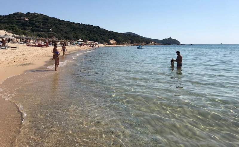 FILE - In this June 29, 2019 photo, people enjoy the white sand and pristine waters of Chia beach, on the Italian island of Sardinia, Italy. Italian media on Saturday, June 5, 2021 said customs police on the Mediterranean island issued fines of up to 3,000 euro ($3,600) to 41 persons who in recent days tried to leave the island with a total of some 100 kilos (220 pounds) of sand, seashells and beach rocks.  (AP Photo/Karl A.Ritter)