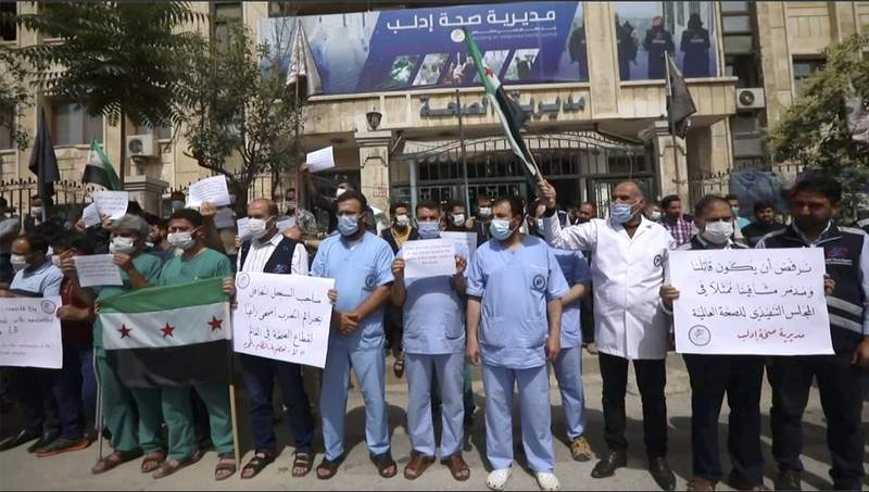 In this image taken from video, dozens of medical workers protest a decision to grant Syrian President Bashar Assads government a seat on the executive board of the World Health Organization, Monday, May 31, 2021, in Idlib, Syria.  (AP Photo)