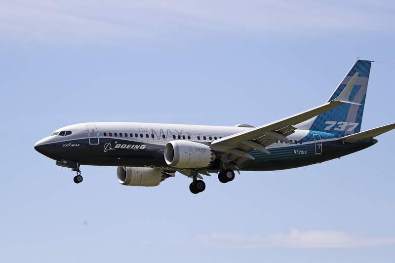 FILE - In this Monday, June 29, 2020 file photo, a Boeing 737 MAX jet heads to a landing at Boeing Field following a test flight in Seattle, USA. Europes flight safety authority says the first flight tests for the Boeing 737 Max, which has been grounded worldwide after two deadly crashes revealed design issues with the jet, have now been completed. (AP Photo/Elaine Thompson, file)