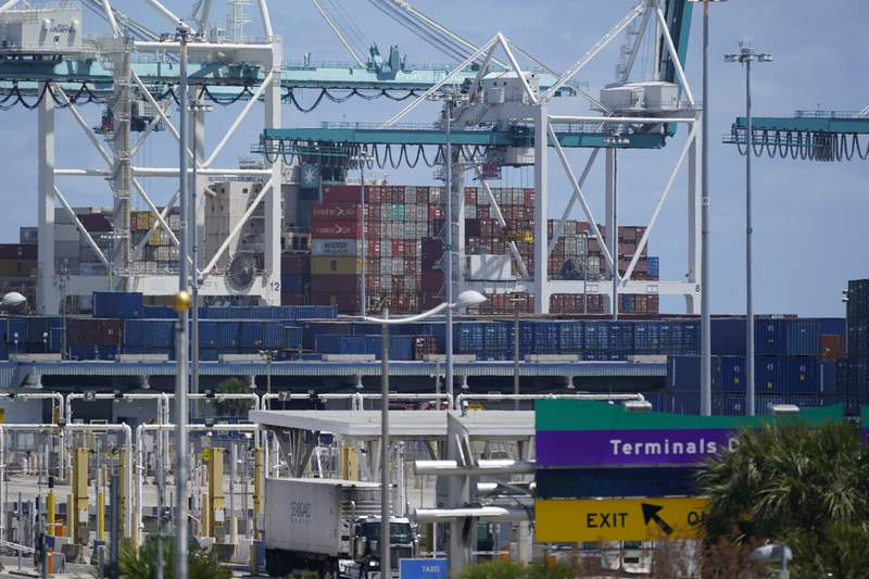 In this April 9, 2021 photo, cargo containers are shown stacked near cranes at PortMiami in Miami.  The U.S. trade deficit narrowed slightly to $70.1 billion in July as economic recovery overseas helped boost American exports while imports declined. The Commerce Department reported Thursday, Sept. 2,  that the trade deficit fell 4.3% in July after surging to $73.2 billion in June.   (AP Photo/Wilfredo Lee)